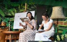 Dwie siedzące kobiety z otwartymi książkami w rękach. Z lewej strony stolik i plakat, z prawej stojąca lampa.